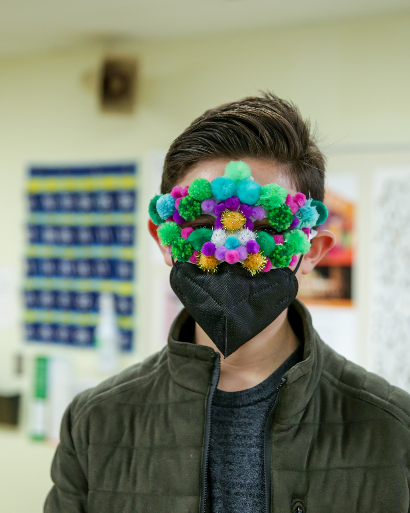 Student Wearing Mardi Gras Mask with Pom Poms